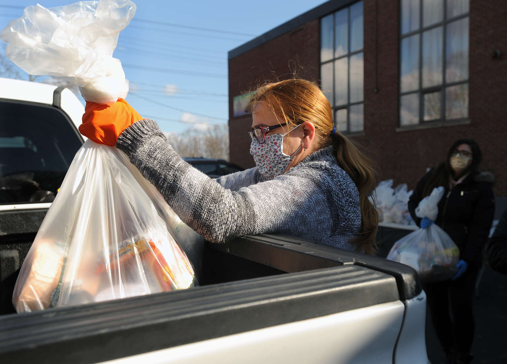 4/17/20-- FRAMINGHAM-- At the Brazilian American Center food distribution center on Waverly Street, Elaine Goncalves puts food into the truck of a client.  The hours are 9 a.m. to 12 p.m. Wednesday and Fridays. [Daily News and Wicked Local Staff Photo/Art Illman]