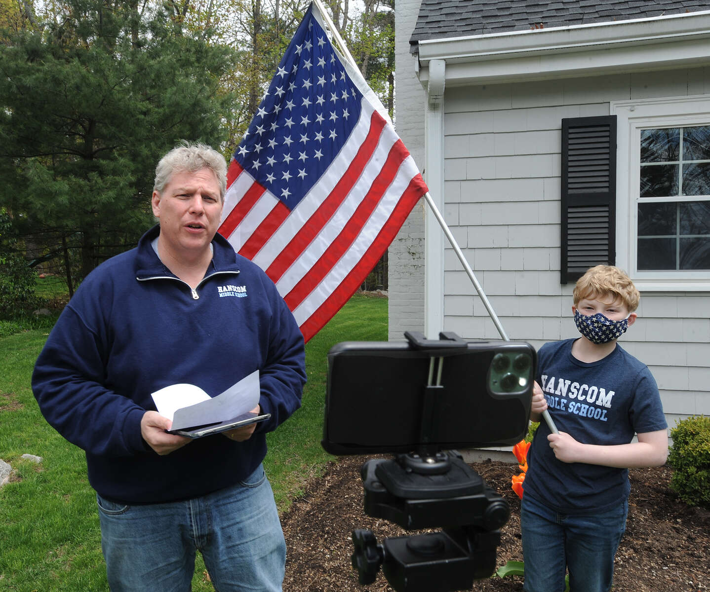5/12/20-- SUDBURY-- Hanscom Middle School Principal Erich Ledebuhr records morning announcements Tuesday with help from his son, Kurt, 12, on his front lawn.  [Daily News and Wicked Local Staff Photo/Art Illman]