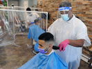 5/26/20-- FRAMINGHAM-- With plastic sheeting, gloves, masks, and faceshield, Papalote Estilo Barbershop owner Levi Bautista gives Rafael Chavez a haircut Tuesday, May 26, 2020 at the Waverly Street shop.  It was the first day the shop has been open since the coronaviorus pandemic began. [Daily News and Wicked Local Staff Photo/Art Illman]