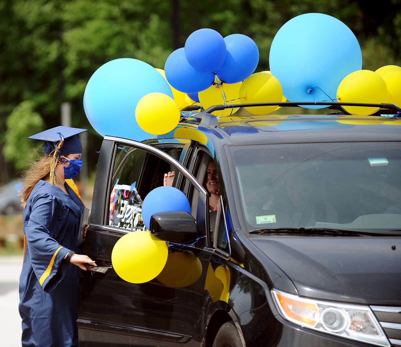 6/5/20-- LEXINGTON--  Julia Anderson, of Belmont, gets back into the car after receiving her drive-up diploma at Minuteman High School Commencement Ceremonies held Friday. [Daily News and Wicked Local Staff Photo/Art Illman]