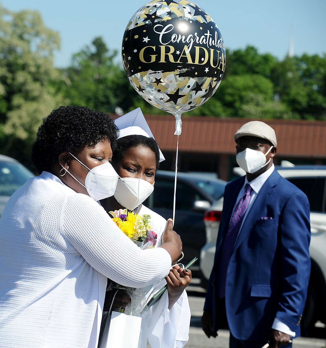 6/4/20-- FRAMINGHAM-- Saint Bridget School held a physically distanced outdoor graduation for 27 eighth grade graduates Thursday morning. Pictured, graduate Carolyn Nakawungu, of Framingham, is congratluated by mom Beatrice, with dad William in the background. [Daily News and Wicked Local Staff Photo/Art Illman]