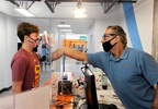 7/6/20-- FRAMINGHAM-- Phase 3 of Massachusett's reopening plan allowed fitness clubs to reopen with new guidelines. Evolve Fitness and Studios opened at 6 a.m. Monday. Pictured, front desk associate Frank Saldi, right, takes the temperature of Charlie David, 16, of Southborough. [Daily News and Wicked Local Staff Photo/Art Illman]