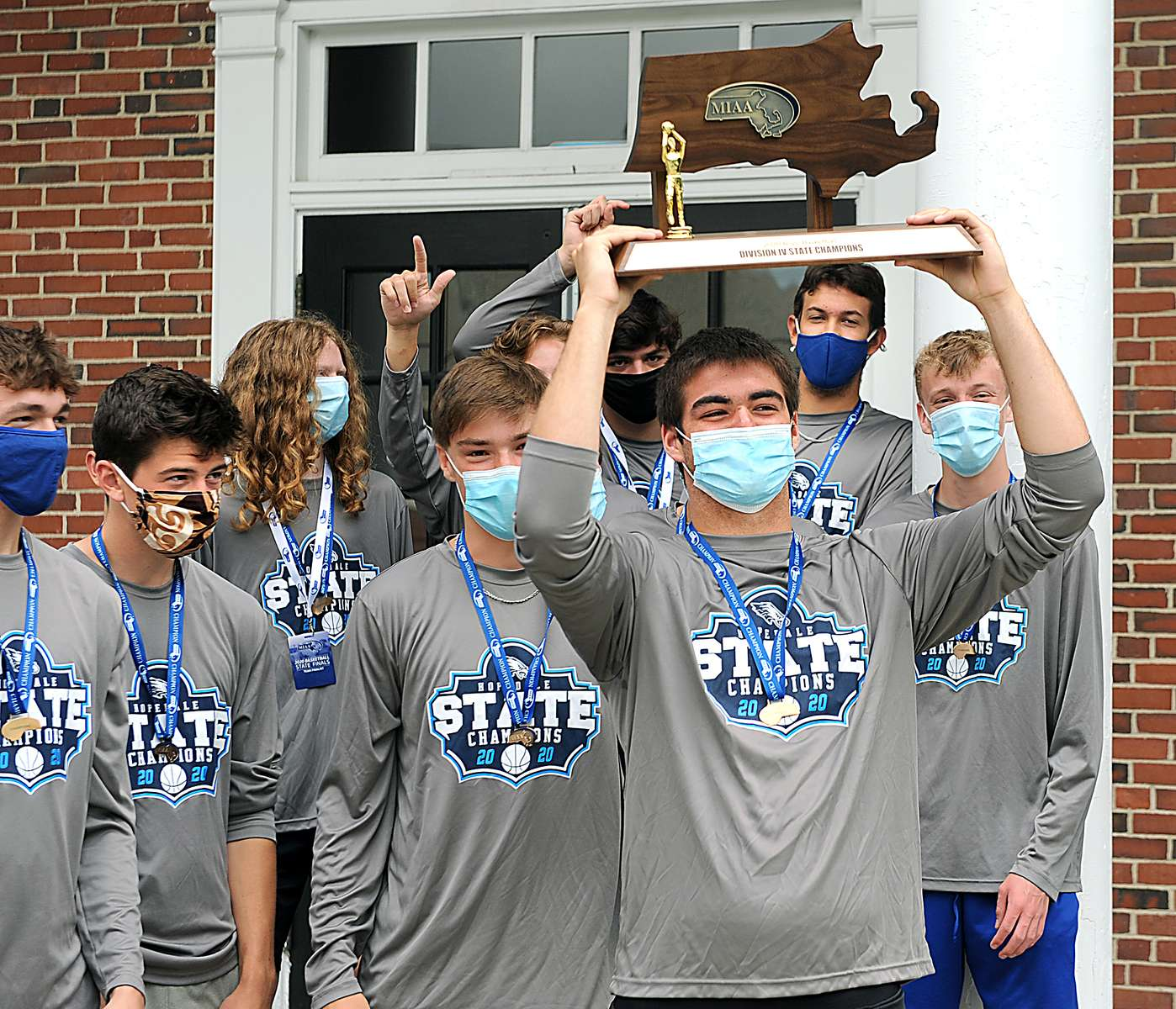 7/8/20-- HOPEDALE-- Hopedale High School boys basketball team captain Dan Liberatore hoists the co-state championship trophy outside the Draper Gym Wednesday morning. [Daily News and Wicked Local Staff Photo/Art Illman]