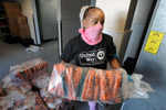 7/23/20-- FRAMINGHAM-- Clara Rodriguez, United Way of Tri-County Pearl Street Cupboard and Cafe warehouse supervisor, moves 50-pound bags of carrots into the refrigerator with Richard Stokes, not pictured, Thursday morning. [Daily News and Wicked Local Staff Photo/Art Illman]