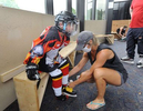 8/13/20-- MARLBOROUGH-- Sarah Argentieri of Shrewsbury laces up the skates of her 9-year-old son, Orazio, in a new socially distanced blocked off area in the lobby of the New England Sports Center before his private lesson on the ice Thursday. Locker rooms are closed so players arrive dressed in their uniforms.  [Daily News and Wicked Local Staff photo/Art Illman]