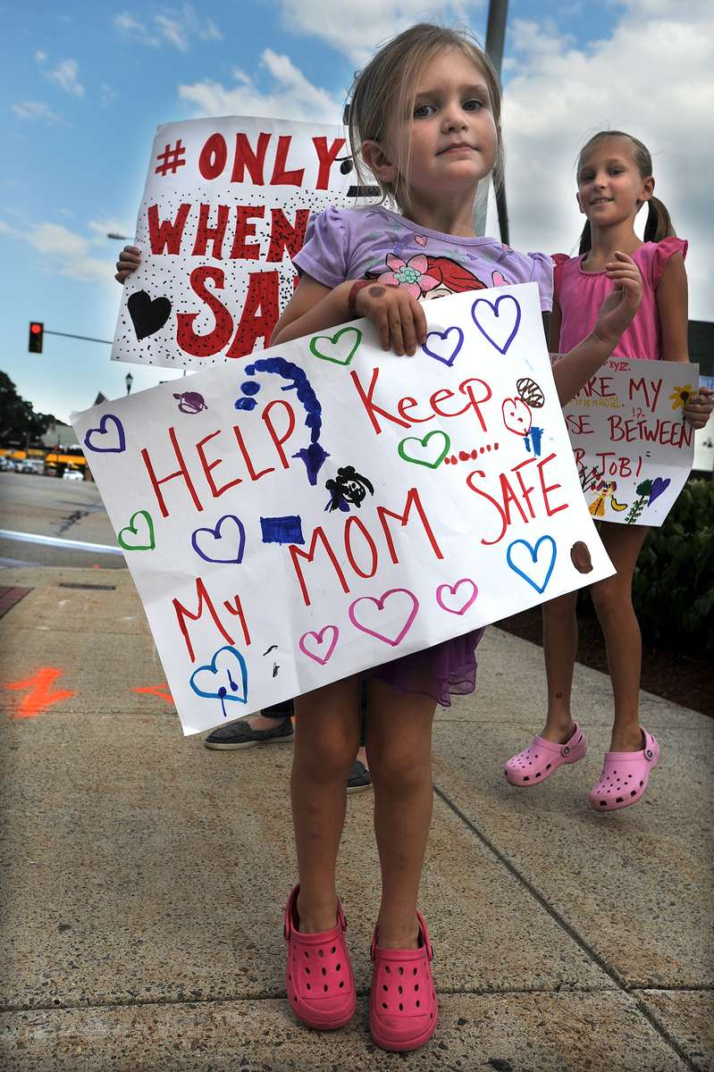 8/19/20-- MARLBOROUGH--  Bridget Fenneuff, 5, daughter of Marlborough High School math teacher Megan Fenneuff, holds signs with her mom, and sister Samantha, 8, as Marlborough teachers assembled at Union Common  Wednesday afternoon to demonstrate against going back to school.  [Daily News and Wicked Local Staff Photo/Art Illman]