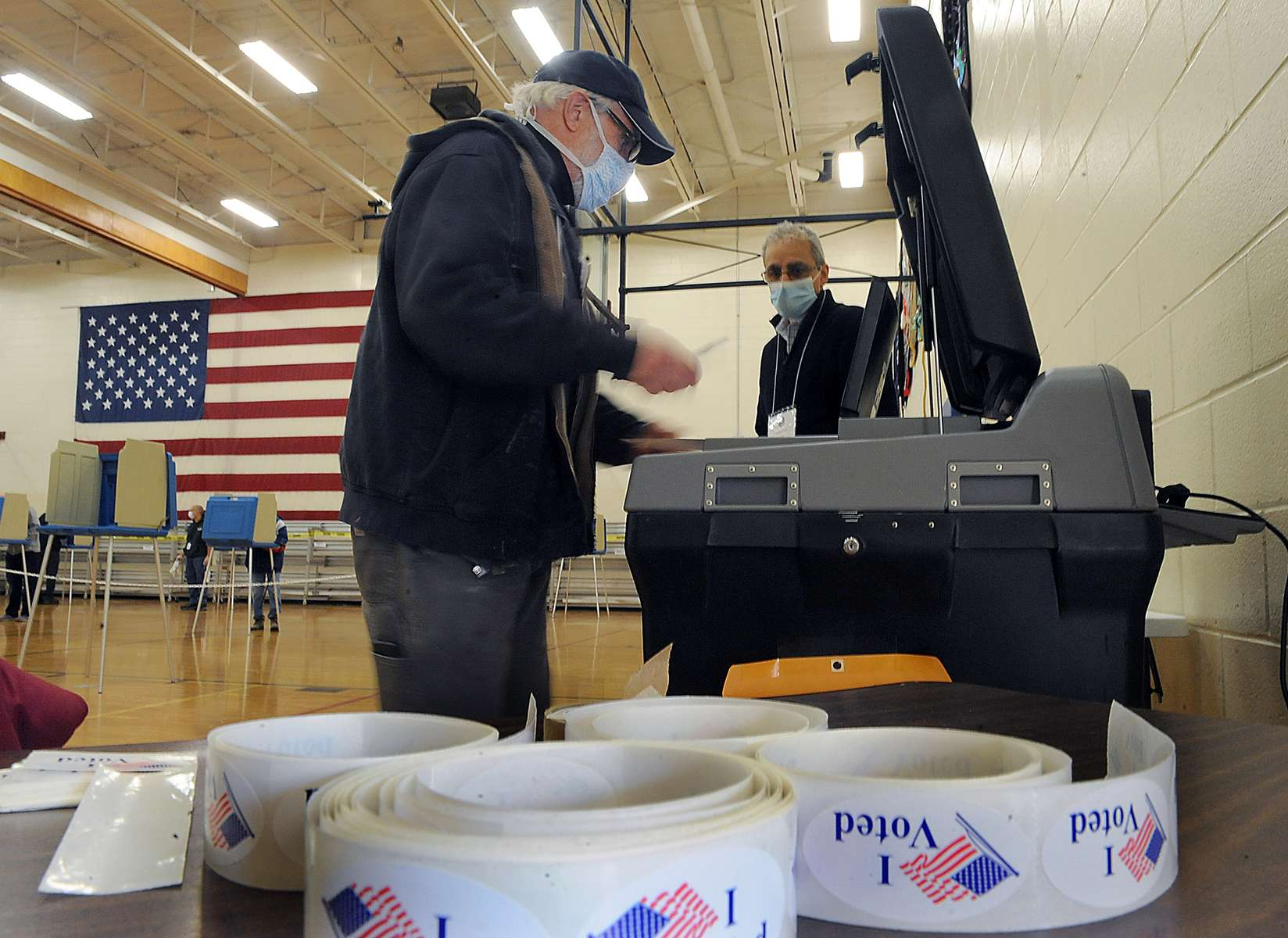 Northborough resident John Derienzo casts his ballot at the Melican Middle School voting place Nov. 3, 2020.  At right is election worker AJ Incorvaia.  [Daily News and Wicked Local Staff Photo/Art Illman]