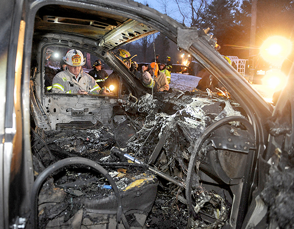 12/12/13 HUDSON-- with jeff m storyFire Chief John Blood looks into the pick up truck which caught fire on Chapin Road Thursday afternoon.Daily News Staff Photo/Art Illman