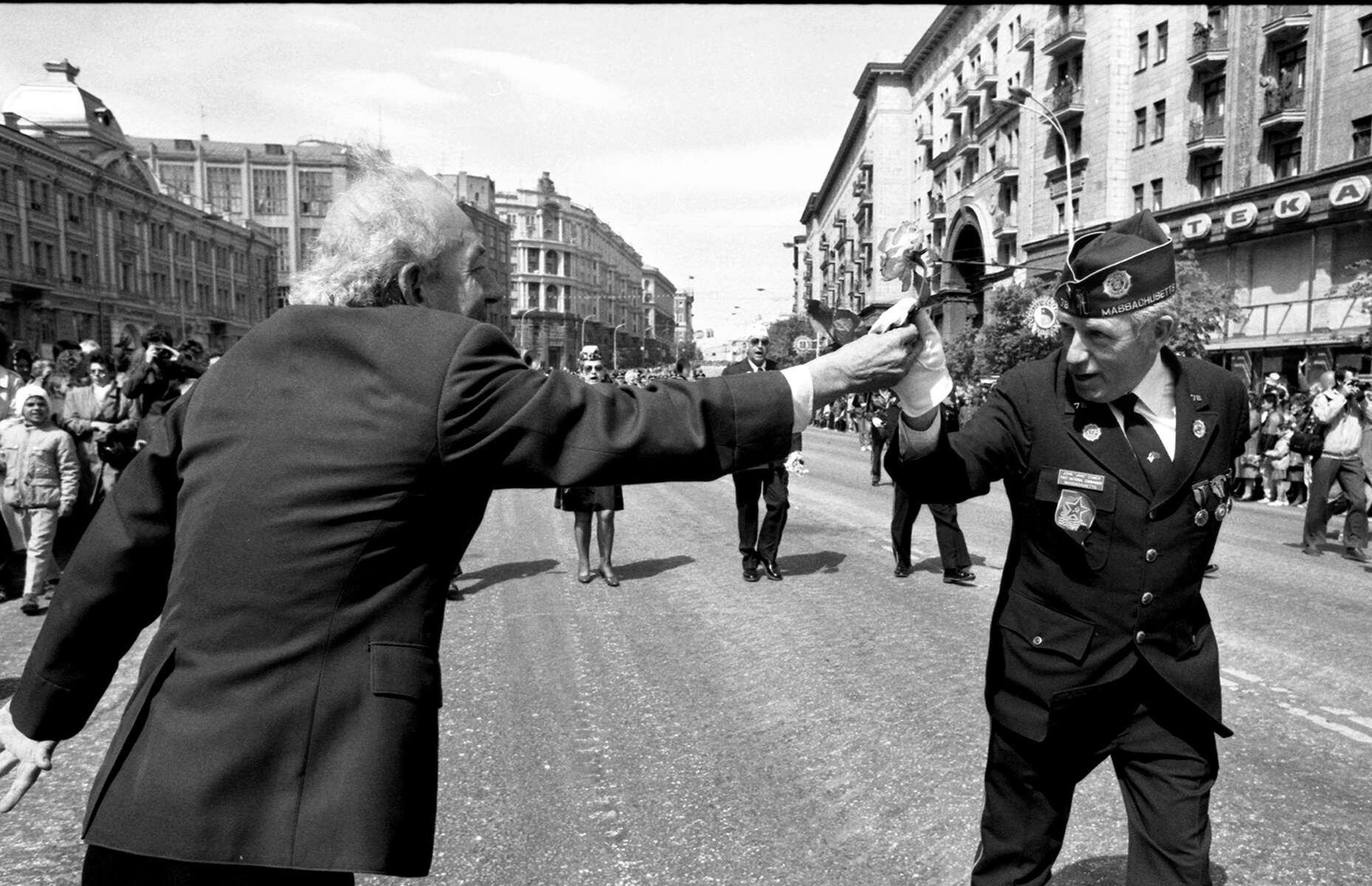 John P. {quote}Jake{quote} Comer, of Quincy, Past National Commander of the American Legion, takes a flower from a Russian citizen during the Victory Day Parade in Moscow in 1990. [Daily News and Wicked Local Staff Photo/Art Illman]