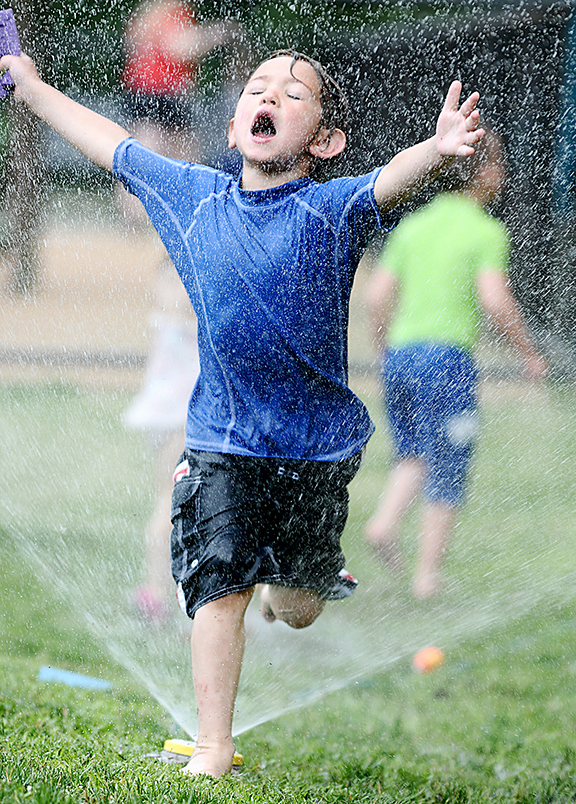 6/18/14--  NATICK--  hot fun in the (almost) summertime--Nathan Churchill, 4, runs through a sprinkler at the Natick Pre School Wednesday at Natick High School.Daily News Staff Photo/Art Illman