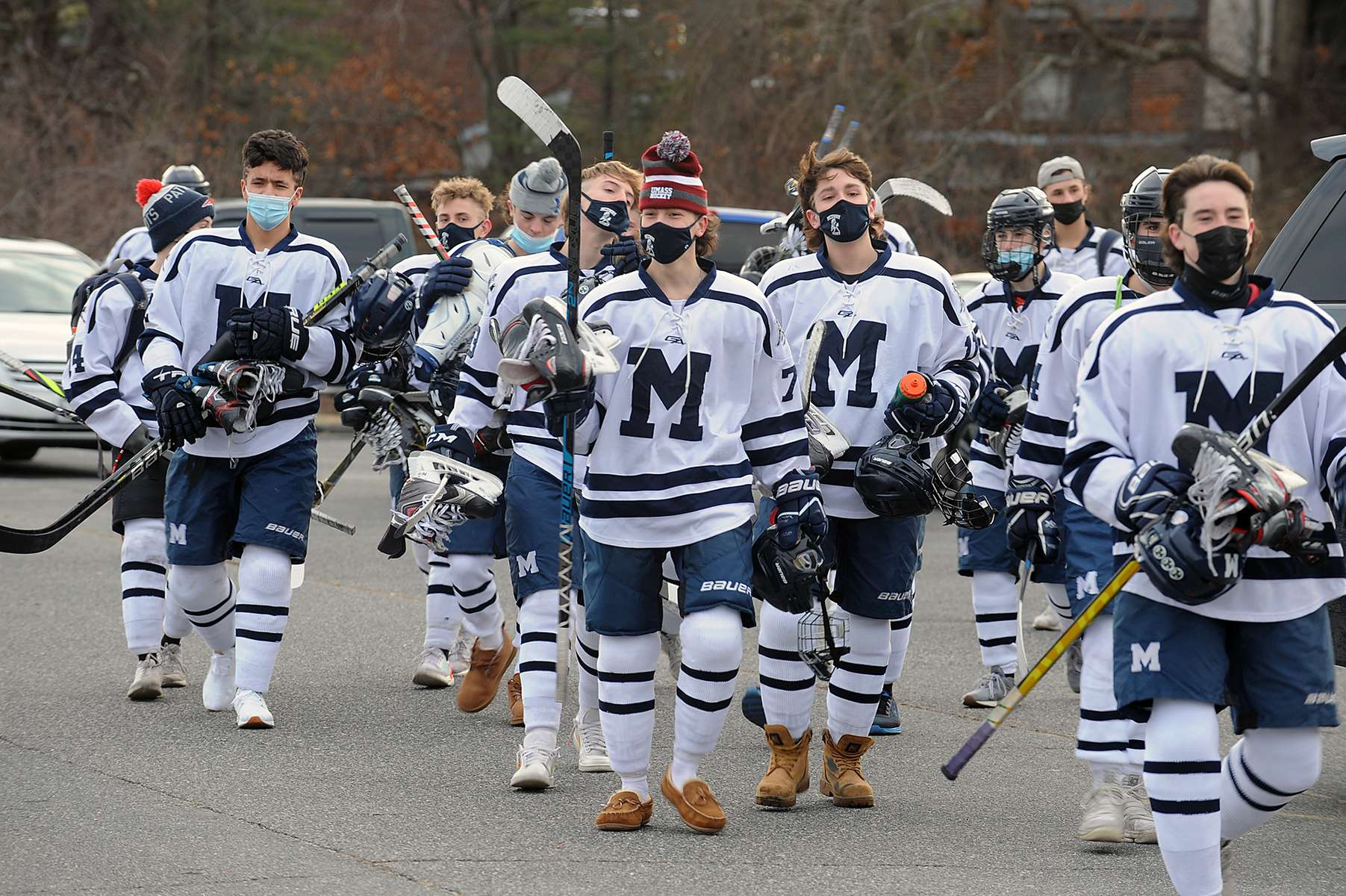 The Medway High  School hockey team marches through the parking lot to Pirelli Veterans Arena in Franklin, Jan. 6, 2021. The locker rooms are closed due to the COVID-19 pandemic. Medway played its season opener against Bellingham.