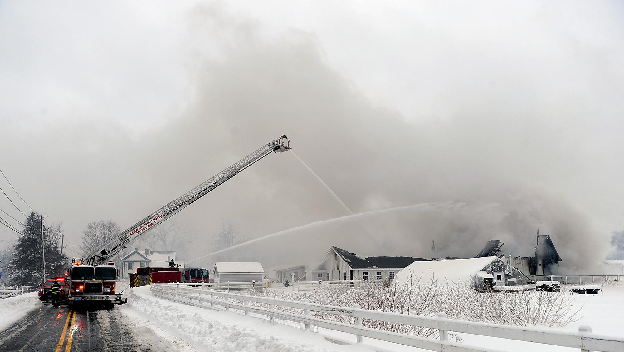 Firefighters pump water on a barn fire at the Hillside School farm in Marlborough, Feb. 2, 2021.
