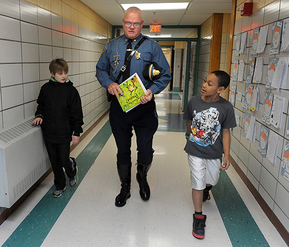 10/24/13-- MARLBOROUGH--  At Community Reader Day at the Jaworek Elementary School Thursday, Mass. State Police Lt. Jim Murphy, who's own children attended Jaworek, is escorted to the class of Becky Kaija by fourth graders Lucas Racki, left, and Malazhi Strothers. More than 30 community leaders read to students.  Murphy's book was What Does It Mean To Be Present, by Rana DiOrio.Daily News Staff Photo/Art Illman