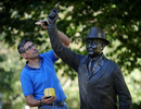 """Hopkinton sculptor Michael Alfano applies wax to his sculpture, """"The Starter,"""" honoring George V. Brown, Hopkinton's """"first citizen of sport,"""" October 6, 2021,  at the starting line of the Boston Marathon.  Alfano, who has also run the Marathon, spruces up his 2008 sculpture in advance of each race.  The 125th running of the Boston Marathon is Monday, October 11, 2021."""