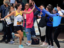 Molly Benson of Boston high fives supporters in Framingham during the running of the 125th Boston Marathon, Oct. 11, 2021.