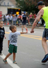 Cruz Florian, 5, and his brother,  Beckam, 7, fist bump runners in Framingham during the running of the 125th Boston Marathon, Oct. 11, 2021.