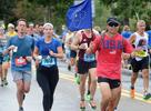 Runners in Framingham during the running of the 125th Boston Marathon, Oct. 11, 2021.