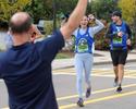 Runner Brooke Connolly, of Boston, spots her dad, Matt Connolly of Wilton, CT, in front of La Cantina Restaurant in Framingham, during the running of the 125th Boston Marathon, Oct. 11, 2021.  At right is runner Brett Phillips, of Boston.