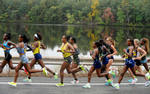 The lead pack of women runners pass Fisk Pond in Natick, during the running of the 125th Boston Marathon, Oct. 11, 2021.