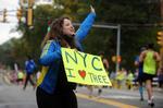 Dana Shulman, of New York, cheers on runners in Natick during the running of the 125th Boston Marathon, Oct. 11, 2021.