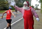 Santa Claus, (Jim Scott, of Natick) cheers on runners in Natick during the running of the 125th Boston Marathon, Oct. 11, 2021.