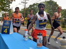 Elite runners pick up their personal water bottles  in Framingham during the running of the 125th Boston Marathon, Oct. 11, 2021.