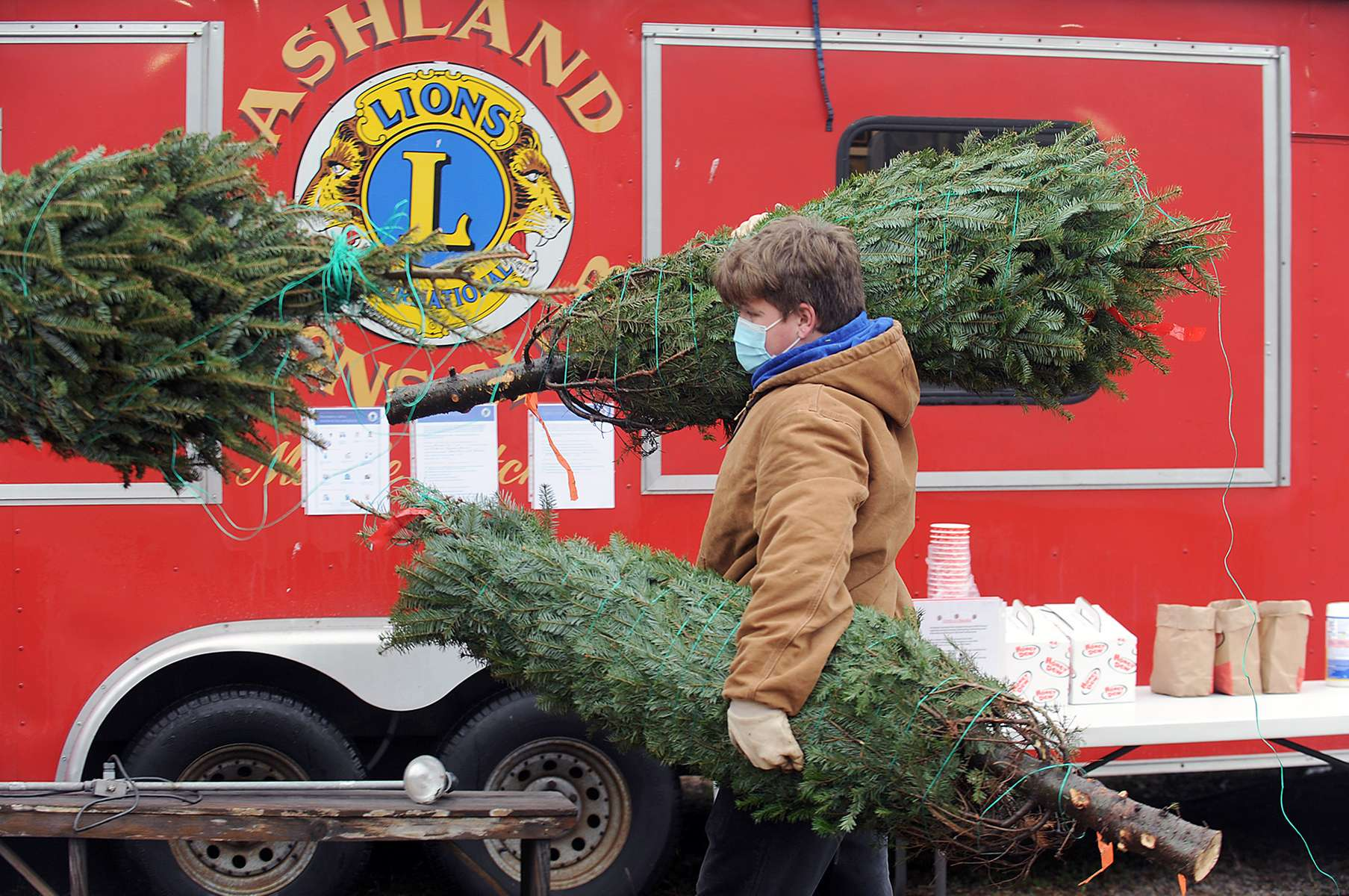 Ashland High School football player Patrick DesLauriers carries one of 700 Maine Christmas trees he and teammates unloaded  Nov. 27, 2020 for the Lions Club annual tree sale at 130 Pond St. which is open 3-6 p.m. Monday through Friday and 9 a.m. to 8 p.m. on weekends.