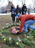 Jill Federman, of Hingham, Lisa Mazerollen, of Easton, and Michelle Pepe, of Sharon, all who recently lost their fathers to COVID-19, watch as David Vaughn, of Natick, places a wreath in  the Floral Heart Project on the Natick Common, March 1, 2021.