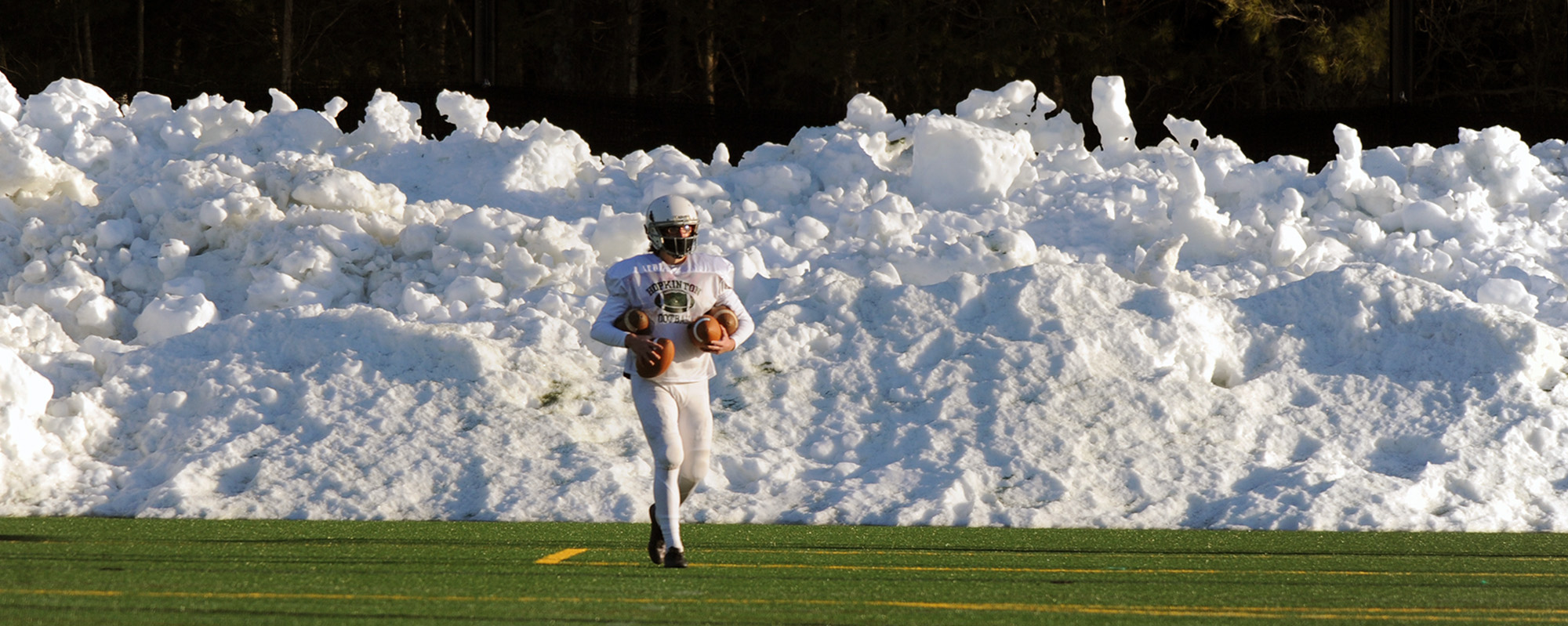 Hopkinton High School sophomore Avery Ravech, the punter and placekicker on the football team, collects balls at practice on the lower turf field, March 8, 2021.