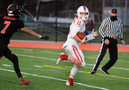 Holliston senior Christian Schneeloch looks back en route to a touchdown at Wayland High School, April 23, 2021.