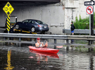 7/28/14-- FRAMINGHAM-- Patrick Primevara didn't miss the chance to kayak on Rte. 9 Monday morning in the eastbound lane, while in the westbound lane one of three stranded vehicles is towed from the water under the Rte.126 bridge. Torrential downpours caused ponding there Monday morning at about 9 a.m.  Traffic was stopped in both directions causing  backups for miles.Daily News Staff Photo/Art Illman