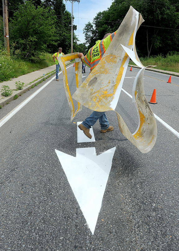 7/9/14-- NATICK--  Natick Department of Public Works employee Paul Holmgren pulls away a stencil during line painting Thursday on Hartford Street.  He also sprinkled glass beads on the wet paint which provides a reflection at night, he said.Daily News Staff Photo/Art Illman