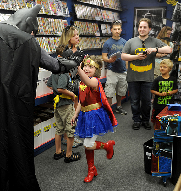 7/23/14-- SOUTHBOROUGH--  At The Hall of Comics in Southborough, (Wonder Woman) Harley Davis, 5, of Hudson, high fives Batman, (Spencer Doe), at Batman Day at the new comic book store. Dozens of fans turned out to celebrate Batman's 75th birthday and to meet Robin, Batgirl, and Nightwing.Daily News Staff Photo/Art Illman