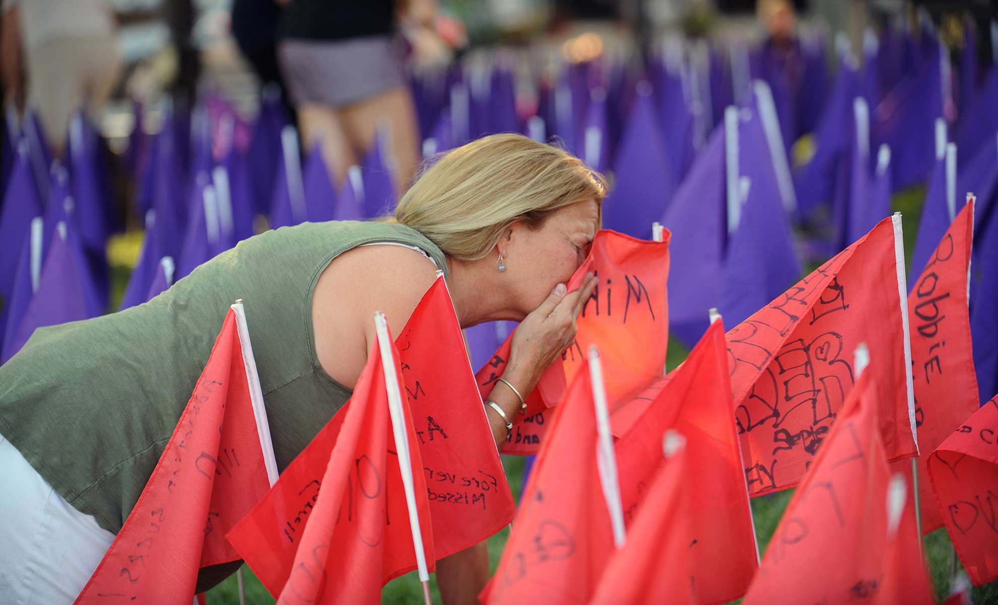 8/21/20-- On the lawn of the First Congregational Church in Natick Friday evening, Theresa Reddish, of Natick, kisses a flag in memory of her son, Michael Reddish, who died in 2017 of a fentanyl overdose. Purple flags were placed on the church lawn in advance of Opioid Awareness Day August 31. There were 2, 015 opioid overdose deaths in Massachusetts in 2019.  [Daily News and Wicked Local Staff Photo/Art Illman]