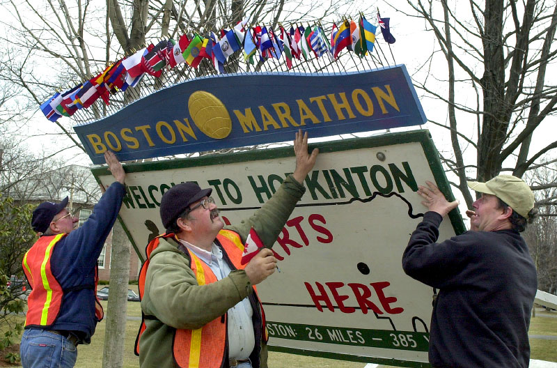 In 2001, Hopkinton DPW workers  from left, Frank Wilie; Louis Mongiat; and Stephen Fant erect the official sign of the Boston Marathon on the town common.