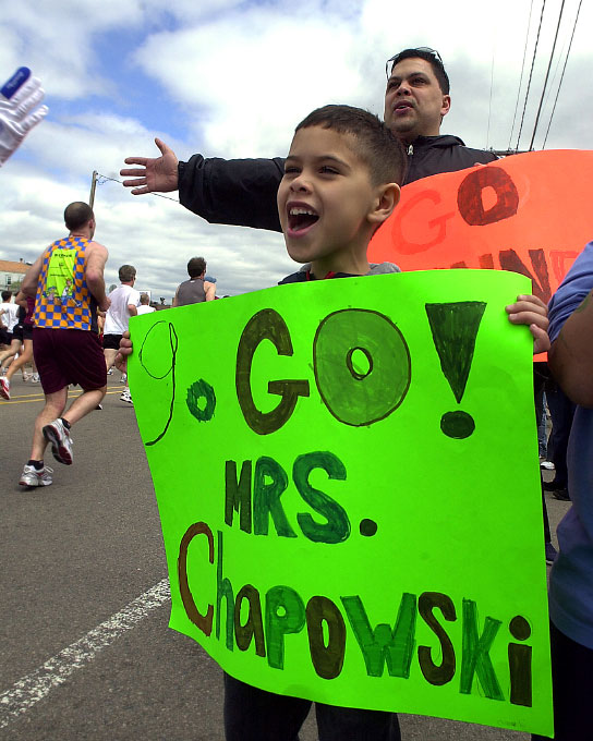 In 2006, Daniel Vazquez, 7, of Framingham, cheers for his Dunning School teacher  Mrs. Chapowski.  Behind him is his dad, Orlando.