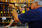 Owner Gary Vickers, center, helps out customer Ron Hajj of Hanover, Mass. as he examines a shotgun Thursday, Dec. 12, 2013 at Smokin' Barrels Gun Shop in Naples. Want the perfect gift for that hard-to-please person on your holiday list? How about a gun? Federal and state laws don't forbid it, as long as you are using your own money to buy it, and are not giving it to a minor or someone who is otherwise legally prohibited from owning one. Gun sales nationwide are soaring' they peak around Black Friday' and sales statewide are expected to reach record levels in 2013, about double what they were in 2007. Meanwhile, guns, ammo and other weaponry are appearing in cheery Christmas flyers put out by major retailers.
