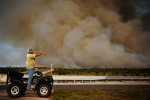 JR Rementeria points to where the fire started the day before at State Road 29 and I-75 eastbound, while a forest fire is seen burning in Big Cypress National Preserve, Collier County Saturday, March 30, 2013.  The so-called Huckabee Wildfire, which started Friday afternoon, has burned through about 20,000 acres on the Big Cypress National Preserve. The resulting smoke caused the Florida Highway Patrol to shut down the Alligator Alley portion of Interstate 75 from about 3 a.m. to 10 a.m. State Road 29 also was shut down from U.S. 41 to Oil Well Road. As of Tuesday, crews had the fire 45 percent contained. Officials said 64 people with multiple agencies were committed to fighting the fire. The Huckabee fire began north of Fire Prairie Trail along Turner River Road and continues to burn to State Road 29 to the west and Interstate 75 to the north. Officials are investigating the fire as a possible arson.