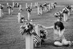 "Sheri McGuire weeps at the headstone of Army Master Sgt. Richard Hughes Burwell Saturday, May 29 at Hillcrest Memorial Park in Augusta. Over 4000 flags were placed at the headstones of past veterans in honoring them for Memorial Day. American Legion Post 178, volunteers and The Boy Scouts of America helped in the efforts. ""He was my surrogate Uncle,"" McGuire said. ""I told him all my secrets, the ones I didn't even tell my parents."" Burwell passed away in 2004."