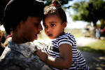 "Pfc. Virniqua Watkins of Sparta, Ga. consoles her teary-eyed daughter Harmony, 1, after a deployment ceremony Friday, Oct. 15, 2010 at Ft. Gordon, Ga. About 100 troops from A Company, 345th Military Intelligence Battalion will deploy to Baghdad, Iraq tomorrow morning at 8:00 a.m. but will head first to training, for six weeks, at Ft. Bragg, N.C. Their mission, the first unit to deploy since the end of combat operations announced last month, will serve as the Corps Analytical Augmentation Element for United States Forces Iraq located at Camp Victory for 12 months. ""Am I going to miss her?"" Watkins said. ""Just look at her."""