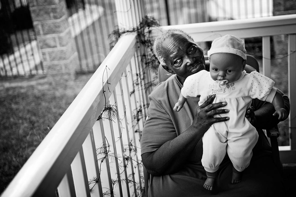 Essie Butler sits on her porch with a baby doll Aug. 26 at her Augusta home on Wrightsboro Road in Augusta. Butler was relaxing talking with a friend watching cars go by.
