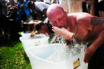 Eric Autler pulls out a pigs foot using his teeth during the bobbing portion of competition July 10 at the Redneck Games in East Dublin. Autler failed to repeat as champion from the previous year.