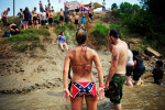 Mallory Robinson of Warner Robins, Ga. adjusts her bikini bottom while watching others make their way down a mudslide into the Occone River July 10 at the Redneck Games in East Dublin, Ga.