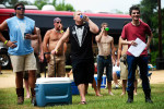 Jacob Hayes, center, of Savannah, Ga. enjoys a beer as opening ceremonies begin July 10 at the Redneck Games in East Dublin, Ga.