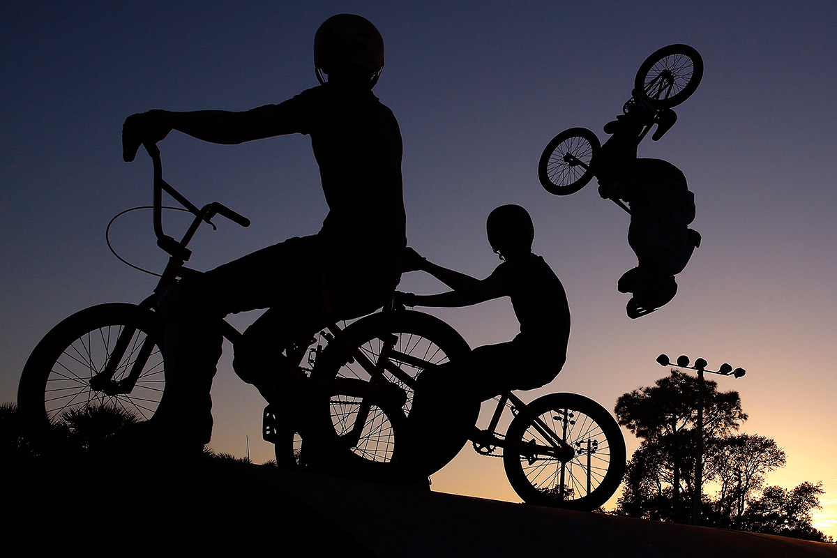 Cole Jordan, 15, from left, and his cousin Tracy Yelvington, 13, both of Fort Myers, look on as Malcow Casas, 15, of Naples hits a backflip on a step up Monday, Dec. 28, 2015 at The Edge Johnny Nocera Skate Park in Naples, Fla. With a high around 85 degrees, extreme daredevils took to the park to try new tricks. This month is one of the hottest Decembers on record. Casas has been racing for two years and freestyle for four. {quote}I like Freestyle better because of the freedom,{quote} Casas said. {quote}With racing it's it's more stress, training – I don't care if I go pro, I just want to have fun.{quote}