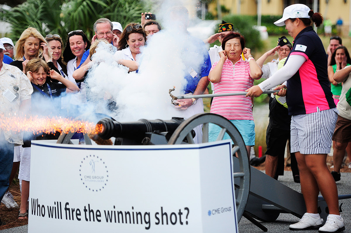 Shanshan Feng, right, starts a new tradition of firing off a cannon to the winner of the CME Group Titleholders LPGA golf tournament Sunday, Nov. 24, 2013 at Tiburon Golf Club in Naples, Fla. Plugging her ears, center is her mother, Yuyan. China's Feng took home the top prize of $700,000 shooting a 15-under par for the tournament. USA's Gerina Piller placed second at 14-under par taking home $139,713. Rounding out third place was Thailand's Pornanog Phatlum at 13-under par taking home $101,352.