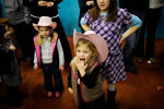 Caroline Cane, 3, center, waits in line next to cousin Abigail Mobley, 3, and Anna Kate Hefner, 9  all of Augusta Saturday, Jan. 22, 2011 at The James Brown Arena in Augusta, Ga. A few thousand came out to watch bull riders brave the beasts for eight seconds of glory.