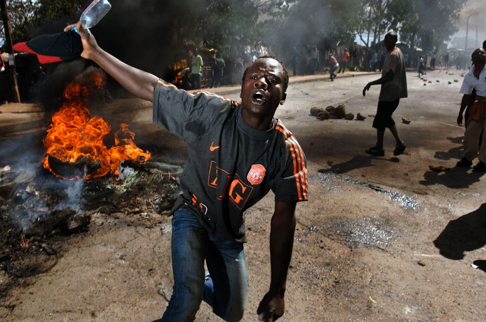 A supporter of Kenya's opposition leader Raila Odinga demonstrates as next to a burning tire in the Kibera slums.