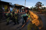 Riot police patrol charge down a street as they try and push back demonstrators in the Mathari slum, Nairobi.