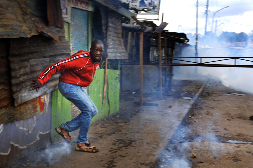 A resident of the Mathare slum of Nairobi tries to get away from Kenyan police as they point their guns at him during clashes in the slum city.